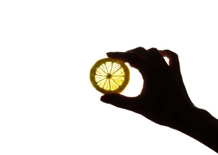 Hand holding a slice of lemon in the light. Close up. Isolated on a white background.