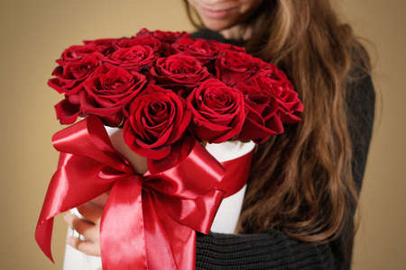 Girl in black jacket holding in hand rich gift bouquet of 21 red roses. Composition of flowers in a white hatbox. Tied with wide red ribbon and bow.