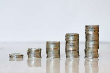 Business Finance and Money concept. Five growing stacks of coins graph. Standing on a reflecting table on a white background.