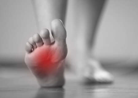 Pain in the foot of a woman. Highlighted in red. On a gray background. Close up.