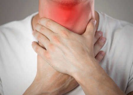 Sore throat in a man. Highlighted in red. On a gray background. Close up. Stock Photo