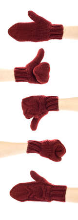A hand in a dark red mitten shows signs. Close up. Isolated on a white background.