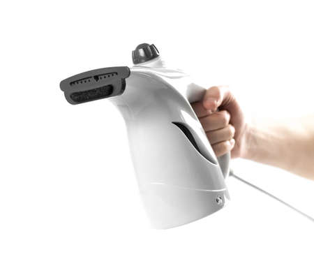 Hand holding a white manual steamer. Close up. Isolated on a white background.