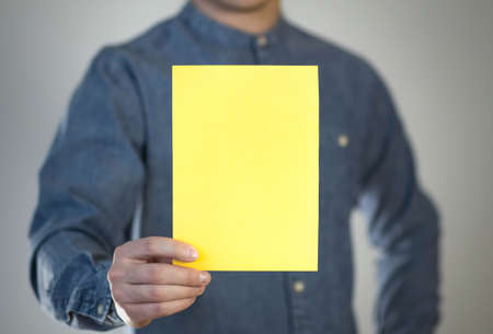 A man holds a yellow piece of paper. A flyer in the hands of a man. Prepared for your text. Isolated on a gray background.