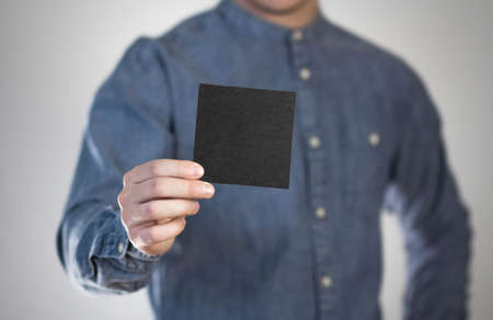 A man holds a black square sheet of paper. A flyer in the hands of a man. Prepared for your text. Isolated on a gray background.