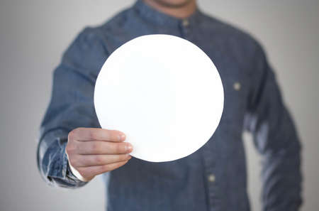 A man holds a white round piece of paper. A flyer in the hands of a man. Prepared for your text. Isolated on a gray background. Banque d'images