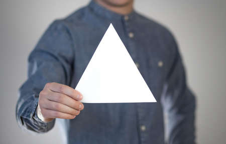 A man holds a white triangular piece of paper. A flyer in the hands of a man. Prepared for your text. Isolated on a gray background.