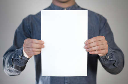 A man holds a white piece of paper. A flyer in the hands of a man. Prepared for your text. Isolated on a gray background.