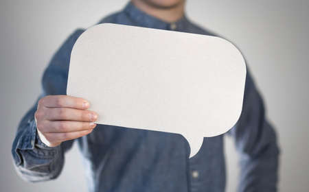 Man holding an empty speech bubble. Close up. Isolated on gray background