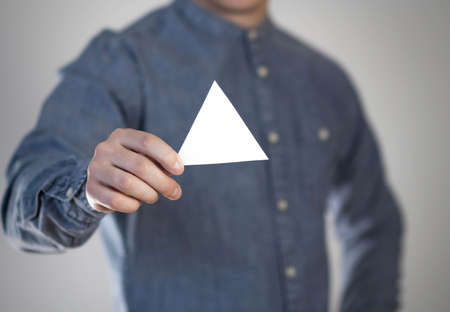 A man holds a small white triangular piece of paper. A flyer in the hands of a man. Prepared for your text. Isolated on a gray background.