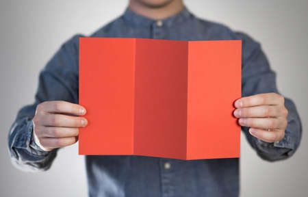 A man holds a red piece of paper. A flyer in the hands of a man. Prepared for your text. Isolated on a gray background. Banque d'images