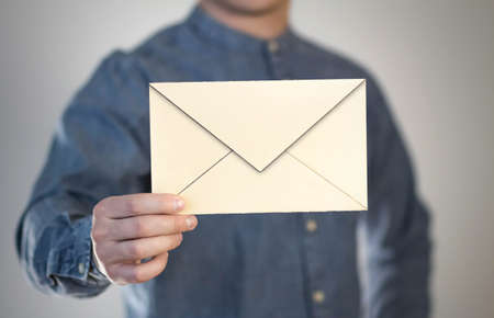 A man holds a paper envelope. The letter is in the hands of a person. Prepared for your text. Isolated on a gray background.