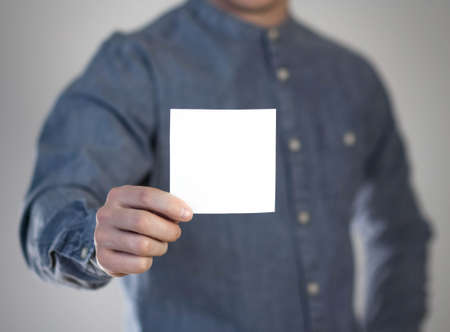 A man holds a white square sheet of paper. A flyer in the hands of a man. Prepared for your text. Isolated on a gray background.