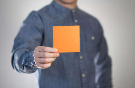 A man holds a orange square sheet of paper. A flyer in the hands of a man. Prepared for your text. Isolated on a gray background.