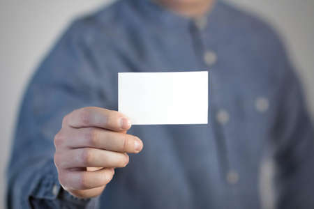 A man holds a white business card. A paper in the hands of a man. Prepared for your text. Isolated on a gray background.