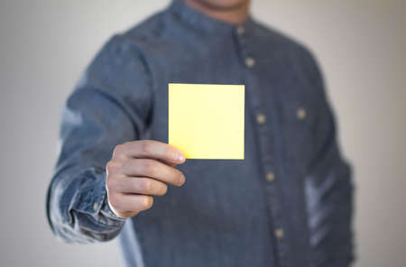 A man holds a yellow square sheet of paper. A flyer in the hands of a man. Prepared for your text. Isolated on a gray background.