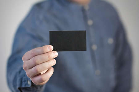 A man holds a black business card. A paper in the hands of a man. Prepared for your text. Isolated on a gray background.