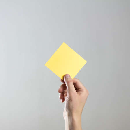 The hand holds an empty square yellow sheet of paper. A clean flyer in your hands. For your text. Isolated on a gray background.