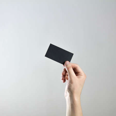 The hand holds an empty black business card. A clean flyer in your hands. For your text. Isolated on a gray background.