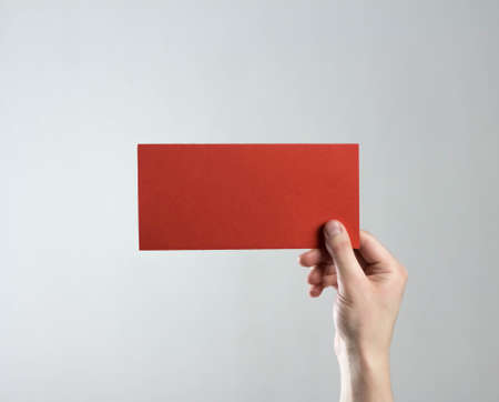 The hand holds a red flyer. A clean flyer in your hands. For your text. Isolated on a gray background.
