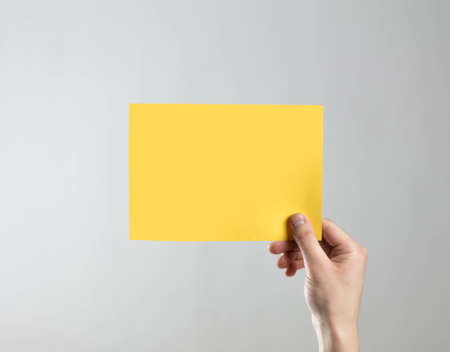 The hand holds an empty yellow sheet of paper. A clean flyer in your hands. For your text. Isolated on a gray background.