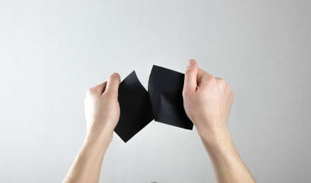 Hands tear up a black sheet of paper. Flyer in hand. Isolated on a gray background.