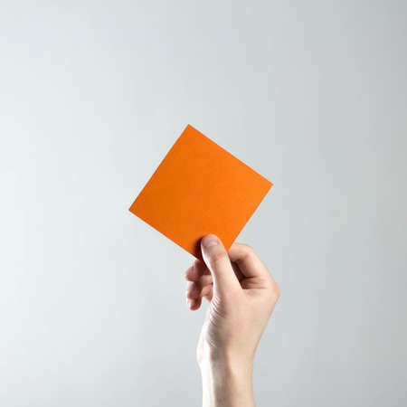 The hand holds an empty square orange sheet of paper. A clean flyer in your hands. For your text. Isolated on a gray background.