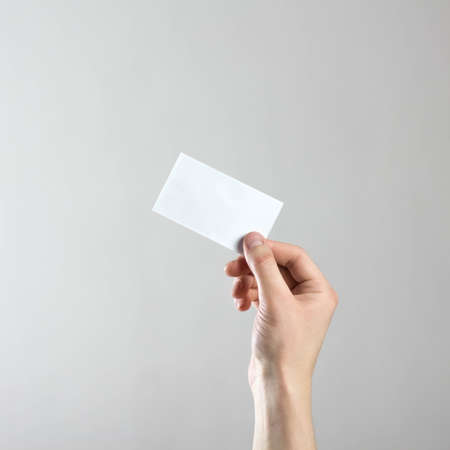 The hand holds an empty white business card. A clean flyer in your hands. For your text. Isolated on a gray background