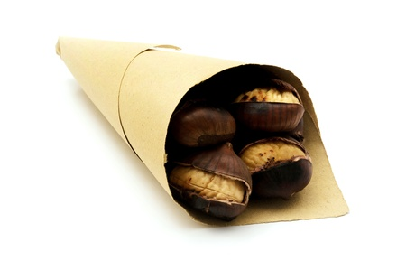 marron: Roasted chestnuts in a paper cone on a white background Stock Photo