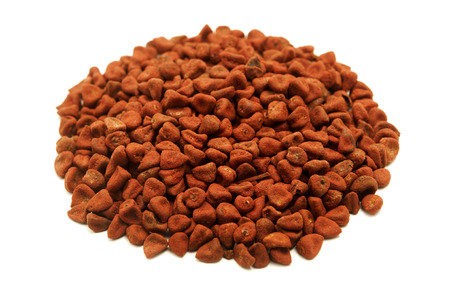 Achiote seeds on a white background