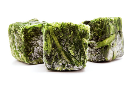 Frozen spinach cubes on a white background