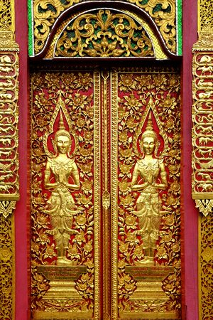 wood door: Wood carvings on a temple door of Wat Fon Soi, Chiang Mai, Thailand Stock Photo