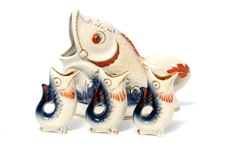 Vintage Soviet fish shaped decanter with shot glasses on a white background