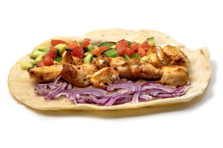 Chicken tikka on lavash with red onions, tomatoes and cucumber a white background