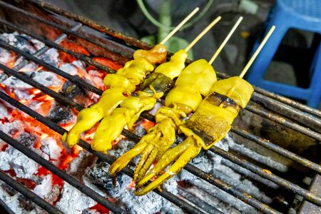 Plaa Mhuk Yang (Thai grilled squids) on a grill