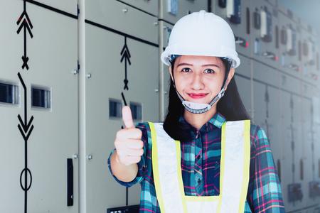 電気機器のチェックとメンテナンスに取り組んでいる女性エンジニア; 女性エンジニアのチェックリストとステータス開閉装置をチェック 写真素材