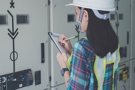 women engineer working on checking and maintenance electrical equipment ;women engineer checking status switchgear with checklist Stok Fotoğraf - 81410170