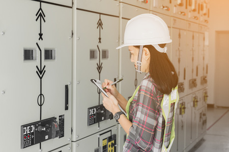 women engineer working on checking and maintenance electrical equipment ;women engineer checking status switchgear with checklist