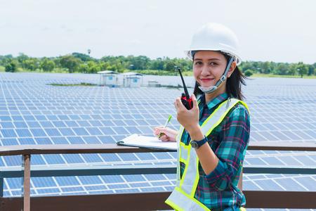 여성 엔지니어 태양 광 발전소에서 일상적인 작업에서 태양 전지 패널 검사 스톡 콘텐츠