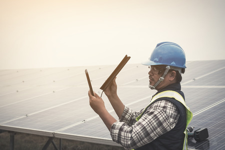 engineer charging his phone with small solar cell at solar power plant