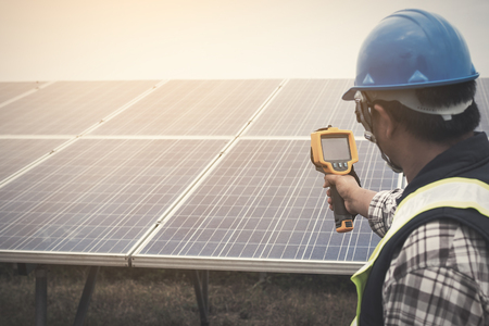 irradiation: engineer or electrician working on  maintenance equipment at industry solar power;  engineer using thermal imager to check temperature heat of solar panel Stock Photo