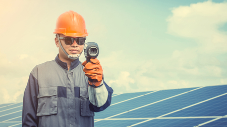 engineer or electrician working on  maintenance equipment at industry solar power;  engineer using thermal imager to check temperature heat of solar panel   Stock Photo