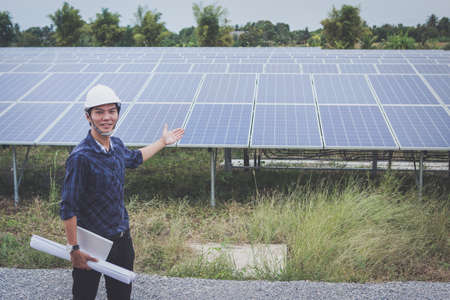 engineer in solar power plant working on installing solar panel ; smart operator holding blueprint for installing equipment in solar power plant