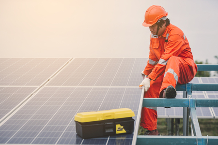 engineer in solar power plant working on installing solar panel ; operation of solar power plant by smart operator