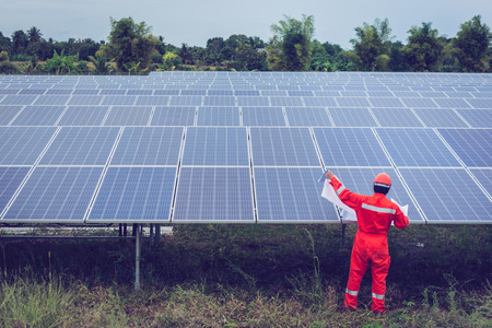 engineer in solar power plant working on installing solar panel ; smart operator holding blueprint for installing equipment in solar power plant Stockfoto