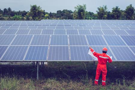 ingegnere in una centrale solare che lavora all'installazione di pannelli solari; operatore intelligente che tiene progetto per l'installazione di apparecchiature in una centrale solare Archivio Fotografico