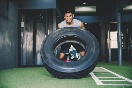 workout concept; young man practicing workout in class ; feeling commitment and patience to weight lifting with big tires