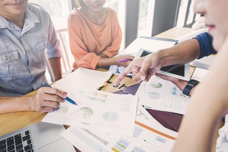 Geschäftsleute diskutieren ein Projekt; Eine Frau, die am Computer sitzt, zeigt ihren Partnern Infografiken; Ein Beispiel für gute Beziehungen bei der Arbeit.