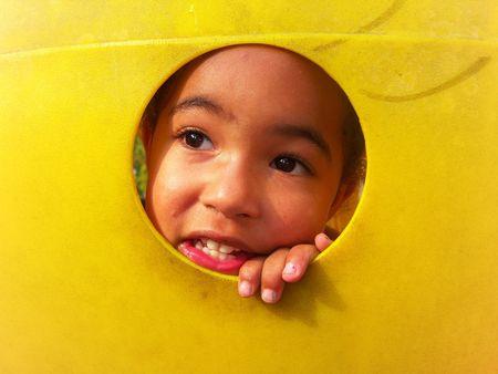 Young child peeking through a hole photo