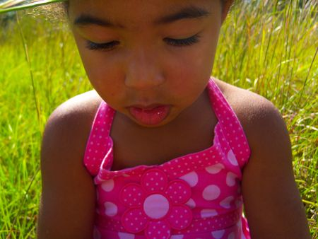 Child Sitting In A Meadow